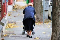 Una mujer mayor de detrás, camina, caminando un cochecillo imagen de archivo libre de regalías