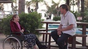 Una mujer mayor en una silla de ruedas está hablando con su marido en el hotel metrajes