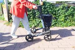 Una mujer mayor está caminando mientras que detiene a un caminante fotos de archivo libres de regalías