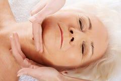 Una mujer mayor está teniendo massgae de una cara. Concepto del balneario. imágenes de archivo libres de regalías