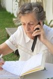 Una mujer mayor está hablando en el teléfono móvil y está tomando algunas notas en su orden del día Imágenes de archivo libres de regalías