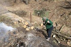 Una mujer mayor limpia una yarda cerca de su casa después de cortar la madera en la leña fotografía de archivo