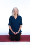 Una mujer mayor medita Foto de archivo libre de regalías