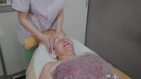 Una mujer mayor miente en un sofá en una clínica de la cosmetología, un cosmetólogo endereza su casquillo almacen de video