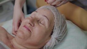 Una mujer mayor miente en un sofá en una clínica de la cosmetología, un cosmetólogo endereza su casquillo almacen de metraje de vídeo