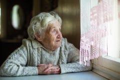 Una mujer mayor mira hacia fuera la ventana que se sienta en su casa imagen de archivo