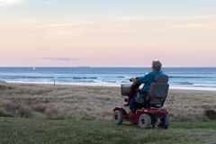Una mujer mayor monta en una silla de ruedas eléctrica parqueada en la playa en el tiempo de la puesta del sol, en una atmósfera  fotos de archivo