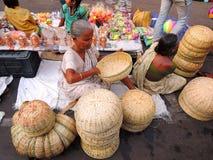 Una mujer mayor pobre que vende las cestas de bambú fotografía de archivo