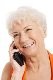 Una mujer mayor que habla a través del teléfono. Imagen de archivo libre de regalías