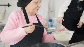 Una mujer mayor que hace las crepes en la cocina Ponga la pasta en la cacerola Otra mujer mayor que detiene a una niña en ella metrajes