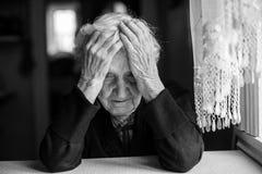 Una mujer mayor que se sienta en la tabla en un estado deprimido Fotos de archivo