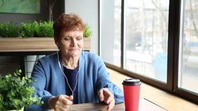 Una mujer mayor que se sienta en un café recuerda su vida almacen de metraje de vídeo