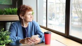 Una mujer mayor que se sienta en un café recuerda su vida metrajes