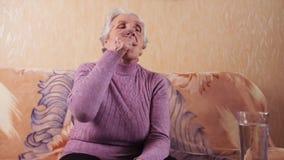 Una mujer mayor que toma la medicación La mujer en la edad de sentarse en el sofá toma una píldora, arrastrada con un vidrio de a almacen de video