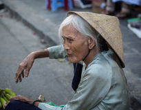 Una mujer mayor que vende mercancías en la calle en Hanoi, Vietnam Imagen de archivo