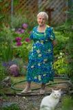 Una mujer mayor se coloca en su jardín Naturaleza Foto de archivo libre de regalías