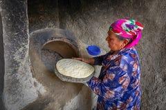 Una mujer mayor se está preparando para introducir el flatbread al moreno Fotografía de archivo