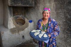Una mujer mayor se está preparando para introducir el samsa al tandoor Imagen de archivo libre de regalías