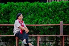 Una mujer mayor se est? sentando en un parque p?blico foto de archivo