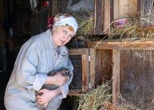 La mujer toma el cuidado de los conejos en la granja foto de archivo