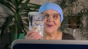 Una mujer mayor utiliza un ordenador portátil para hacer el dinero en Internet metrajes