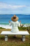 Una mujer Meditating por el mar Imagen de archivo