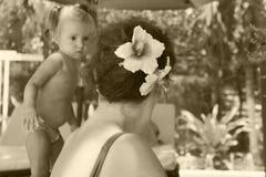 Una mujer mira al bebé la mujer se sienta con ella de nuevo a la cámara La mujer tiene un peinado hermoso la flor hermosa está en foto de archivo