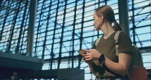 Una mujer mira la pantalla de un teléfono móvil para encontrar su e-boleto en el avión metrajes