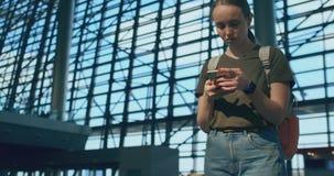 Una mujer mira la pantalla de un tel?fono m?vil para encontrar su e-boleto en el avi?n almacen de metraje de vídeo