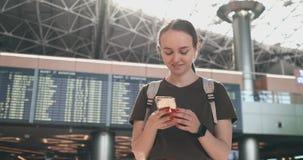 Una mujer mira la pantalla de un tel?fono m?vil para encontrar su e-boleto en el avi?n metrajes