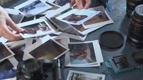 Una mujer mira las fotos impresas del viaje con el mar y el sol, de la extensión en una tabla de madera con la cámara de la foto  metrajes