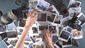 Una mujer mira las fotos impresas del viaje separado en una tabla de madera con la cámara y la lente de la foto almacen de metraje de vídeo