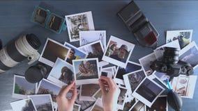 Una mujer mira las fotos impresas del viaje separado en una tabla de madera con la cámara y la lente de la foto almacen de video