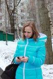 Una mujer mira un teléfono móvil Fotos de archivo