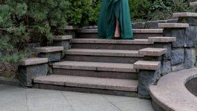 Una mujer misteriosa en un vestido de noche y tacones altos verde Desciende los pasos en el jardín La mujer va una fecha almacen de metraje de vídeo