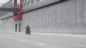 Una mujer monta una motocicleta en un casco almacen de metraje de vídeo
