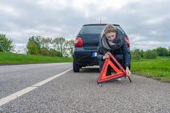 Una mujer monta un triángulo amonestador detrás del coche imagen de archivo libre de regalías