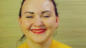 Una mujer morena con una sonrisa alegre en sus liftinges faciales encima de su dedo índice Primer almacen de metraje de vídeo