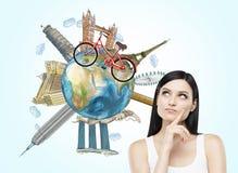 Una mujer morena está soñando sobre viajar El globo con los lugares más famosos del mundo Un modelo de las cruces de la bicicleta Fotos de archivo libres de regalías