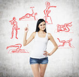 Una mujer morena hermosa en pantalones cortos de un top sin mangas blanco y del dril de algodón que está señalando su finger para Fotos de archivo libres de regalías