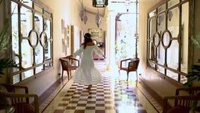 Una mujer morena hermosa está bailando en el vestíbulo Sitio del vintage con los espejos y el un montón de luz metrajes