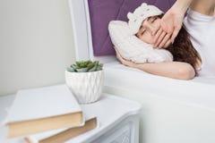 Una mujer morena joven atractiva de la muchacha despierta y sorbe mientras que bosteza en su cama en una máscara del sueño imagenes de archivo