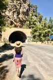 Una mujer morena joven caucásica en un sombrero de paja está caminando hacia un túnel en las montañas Vista posterior, día solead fotografía de archivo