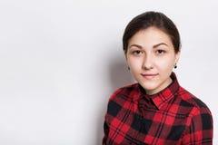 Una mujer morena joven con los ojos trenzados del marrón del pelo y las cejas expresivas vestidos en rojo comprobó la camisa que  Fotos de archivo