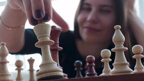 Una mujer morena joven hermosa de Latina con una sonrisa dentuda maravillosa que juega a ajedrez en casa almacen de metraje de vídeo