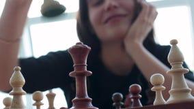 Una mujer morena joven hermosa de Latina con una sonrisa dentuda maravillosa que juega a ajedrez en casa almacen de video
