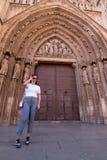 Una mujer morena joven que camina delante de la catedral de Valencia Spain con la camisa blanca y los pantalones grises imagen de archivo libre de regalías
