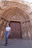 Una mujer morena joven que camina delante de la catedral de Valencia Spain con la camisa blanca y los pantalones grises fotografía de archivo