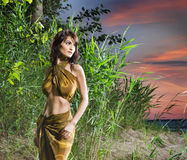 Una mujer morena joven que presenta en selva verde Imágenes de archivo libres de regalías
