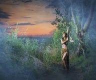 Una mujer morena joven que presenta en un bosque verde Imagen de archivo